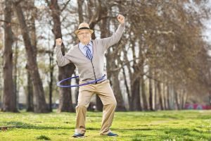 Senior man, exercise with a hula hoop and gesture happiness in park